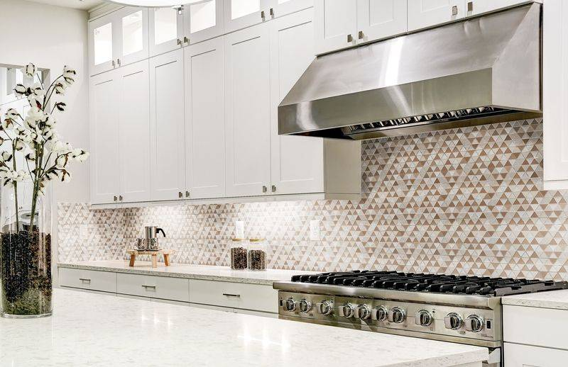 White cupboard kitchen with a neutral countertop and backsplash