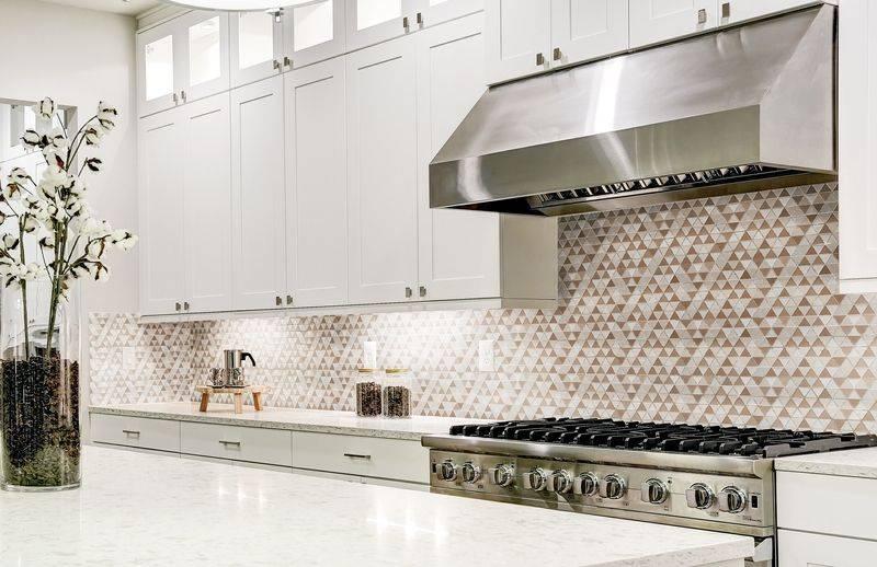 Cuisine aux armoires blanche avec un comptoir et un dosseret de mosaïque neutre
