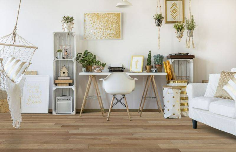Office desk with white and golden decorative items, several plants and a varnished wooden floor.