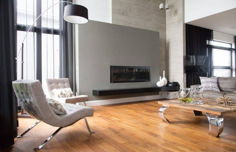 Oiled wooden floor installed in a modern living room with a rustic table and cushions