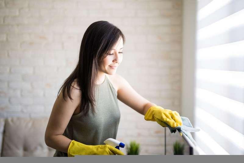 Personne qui nettoie des stores pour retirer de la poussière