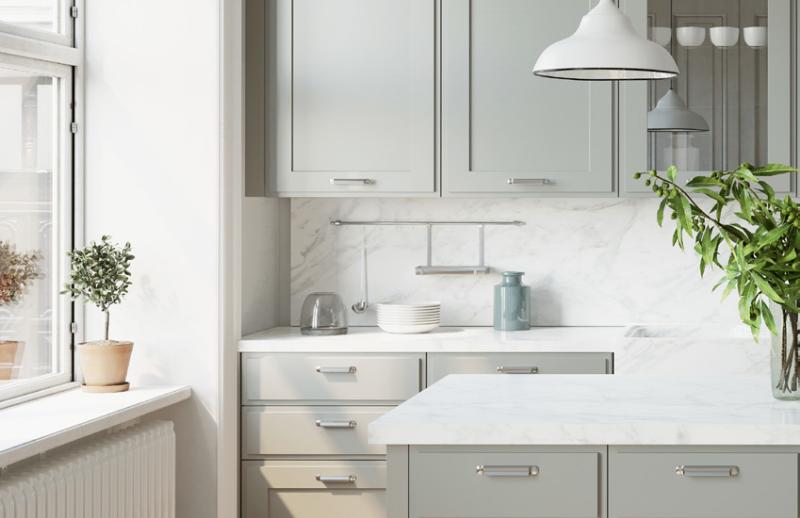 Armoires peinturés avec couleurs pastels dans une cuisine monochromatique blanche